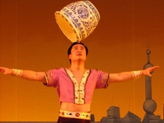 A performer doing a fine job balancing a porcelain pot on his head; Ritz Carlton's Shanghai Center Theater