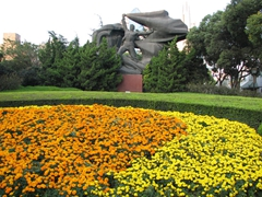 Colorful flowers (even in the middle of winter) surround a Bund statue