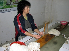 A worker demonstrates the art of stretching incredibly strong silk into thin, translucent layers