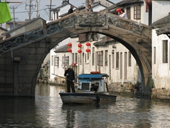 A boat slowly passes under a curved bridge; Suzhou's canal system