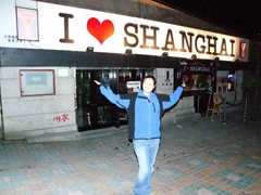 "Becky strikes a silly pose beneath a ""I heart Shanghai"" sign; Bund area"