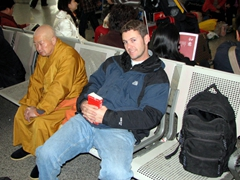 Robby sits next to a saffron robed monk while waiting at the Cheng Du airport