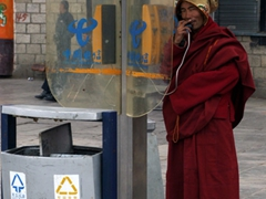 A monk makes a phone call in a telephone booth; Barkhor district