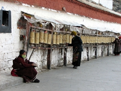 Prayer wheels surround the base of the Potala Palace, and countless pilgrims spin them constantly