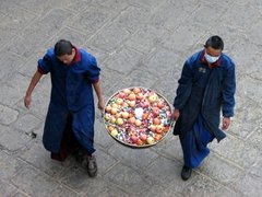 Colorful food donations are carried into the Jokhang temple