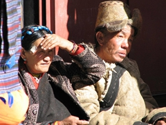 This elder couple huddles together in an effort to seek refuge from the bright, midday sun