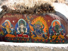 Colorful Gods adorn this large rock; Sera Monastery