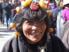 A Tibetan lady smiles broadly while showing off her large amber and turquoise headpiece