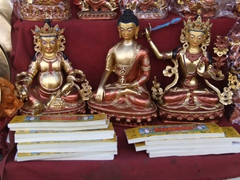 Buddha statues and prayer books on display in street stands