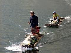 A motorized bamboo raft tugs along a hitchhiker; Li River
