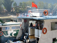 A Chinese flag waves from the back of a boat; Li River