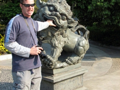 Robby pets a stone lion; Seven Star Park