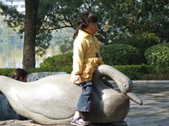 A young girl hops a ride on this stone swan; Banyan Lake