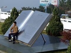 "Ummm, I don't think that's a stool. A Chinese tourist poses on a massive ""book"" detailing the history of the 3 Gorges Dam project"