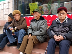 Men around the world must hate shopping! This quartet of elderly men take a breather at the corner while their wives go shopping