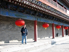 Robby stands beside massive, red lanterns that line the corridor leading to the Feng Shui Museum