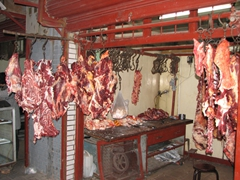 Freshly slaughtered meat hangs for sale in the Muslim District
