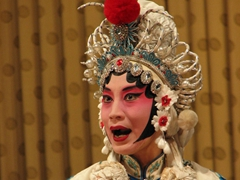 A close up shot of an Opera singer; language barriers are of no concern because it is easy to deduce what is going on with the performer's costumes, facial expressions, and body language