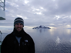 Robby at the stern of the Polar Star with Paulet Island in the background. Paulet is located off the northeastern end of the Antarctic Peninsula, and is composed of lava flows capped by a cinder cone with a small summit crater
