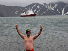 Dr Ross, decked out in South African colored swim trunks, poses at the geothermally heated waters of Deception Island
