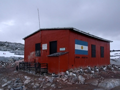 "A bright red ""Armada Argentina"" hut (with an emergency supply of winter gear) greets us at the landing zone on Petermann Island"