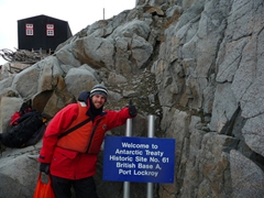 Robby posing beside a sign on the miniscule island of the Goudier, where a restored base and museum can be visited; Port Lockroy