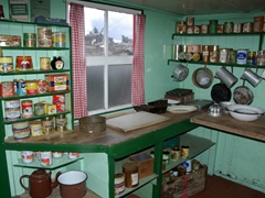 A perfectly preserved kitchen complete with condiments and a window view of nesting gentoo penguins; Port Lockroy Museum