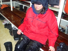 A drenched Becky prepares to take off her wet weather gear for the last time in the mud room after a full day excursion at the incredible Hannah Point on Livingston Island (South Shetlands)