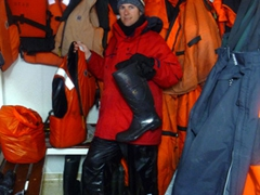 Robby prepares to hang his life jacket and to place his rinsed rubber boots beneath the benches to dry in the mud room; Polar Star