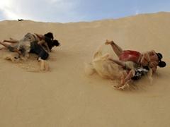 Guys versus girls sand dune rolling contest; Western Sahara