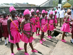 A brightly dressed group of school girls wait patiently for their turn in the parade; Lime Youth Day festivities; Cameroon