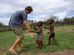 Robby gives two Himba boys a high five; Ohungumure Village, Namibia