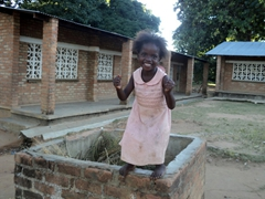 A jubilant girl poses for a photo outside Kande School; Malawi