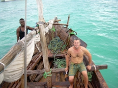 Robby sits at the front of our dhow as we cruise past Zanzibar's beautiful turquoise hued waters; Tanzania