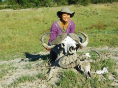 Becky posing with a water buffalo and wildebeest skull; Okavango Delta