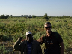 Charles and Robby pose in front of two bull elephants in the distance; Okavango