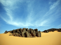 Perfect sand dunes envelop their rocky counterparts to make a beautiful image; Tamgs Kis