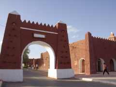 A red mud gate leading to the main square of Adrar
