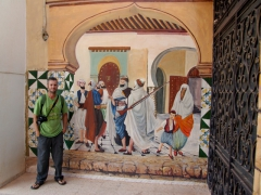 Robby next to a mural depicting an old city scene; Adrar