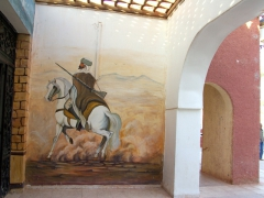 Painted scene on a building lining the main squre of Adrar