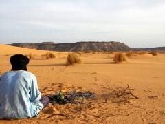 Abdsahlem sits next to the campfire making Tuareg tea; Tiguelguemine