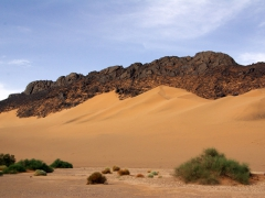 Sand dunes encroaching upon the rocky outcrop formations; Tiguelguemine