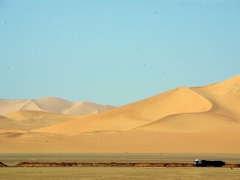 A big cargo truck driving past a massive sand dune helps one gain perspective