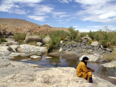 Abdsahlem relaxes next to a guelta in Afilal
