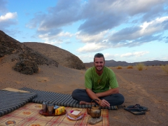 Robby relaxes with a cup of tea while the guys set up the campsite; south of In Salah