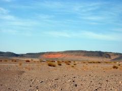 Orange sand peaking through rock formations in the Sahara
