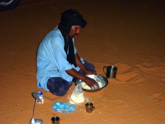 Abdsahlem prepares taguila (a traditional Tuareg meal consisting of bread cooked in the sand mixed with a lamb sauce); MhajebaA