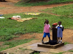 Children take a break from the water pump to wave hello; near Bakeba
