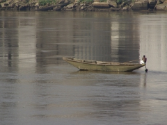 A man paddles his pirogue on a main river in Douala