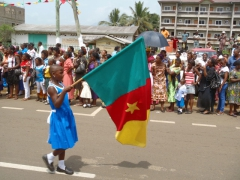 Carrying the Cameroonian flag, a school girl leads her classmates in a parade down Limbe's streets; National Youth Day